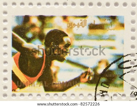 UMM AL-QIWAIN - CIRCA 1973: a stamp from Umm Al-Qiwain shows image of a runner on the track, circa 1973 - stock photo