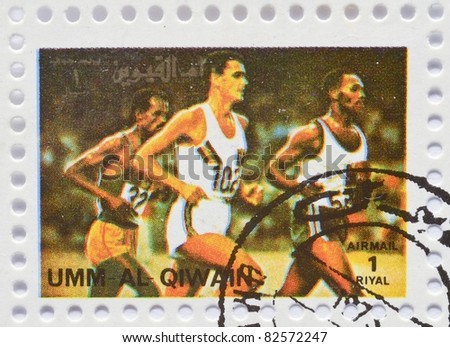 UMM AL-QIWAIN - CIRCA 1973: a stamp from Umm Al-Qiwain shows image of runners on the track, circa 1973 - stock photo