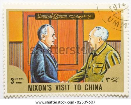 UMM AL-QIWAIN - CIRCA 1972: a stamp from Umm al-Qiwain shows image of US President Nixon meeting Mao Zedong during his visit to China, circa 1972 - stock photo