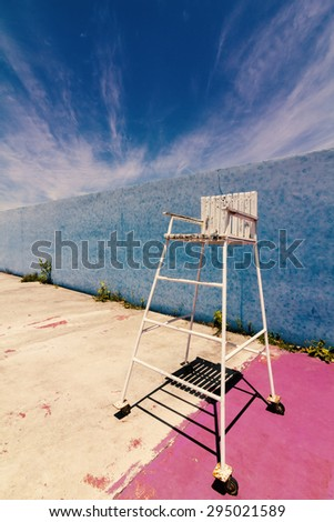 Umpire chair in the old tennis court with blue sky background.Used film filter for old tone color. - stock photo