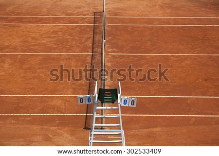 Umpire chair with scoreboard on a tennis court before the game. The playground is empty and the score is zero to zero.  - stock photo