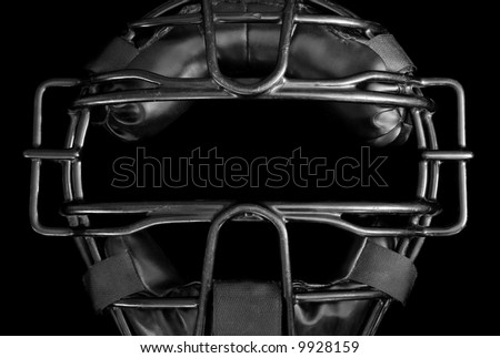 Umpire mask in black and white.  Close-up of well worn, baseball umpire mask on black background. - stock photo