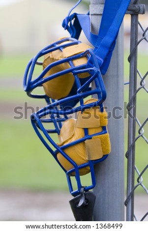 Umpire's mask hanging on backstop post, waiting for game to start. - stock photo