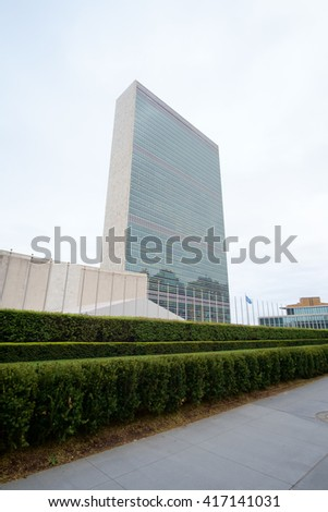 UN United Nations secretariat skyscraper with hedge and partial view of general assembly building in the foreground. Wide angle view. - May 5, 2016, 1st Avenue, New York City, NY, USA - stock photo