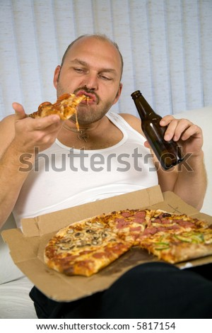 Unattractive overweight man eating a big slice of pizza and drinking beer - stock photo