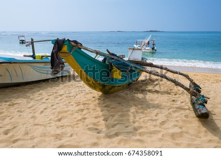 UNAWATUNA, SRI LANKA - DECEMBER 03. Beach of one of the major tourist spots in the south west of Sri Lanka. Tourists do aquatics, outrigger, fishing boats on the beach. Unawatuna on December 03, 2016