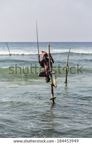 UNAWATUNA, SRI LANKA - JANUARY 25, 2014: Unidentified stilt fisherman at Unawatuna, Sri Lanka. Stilt fishing is special to Galle district and thereare about 500 fishing families in the coastal belt. - stock photo
