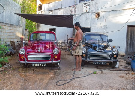 UNAWATUNA, SRI LANKA - MARCH 6, 2014: Local man washing two Morris Minor cars in the yard with water hose. There are estimated to be as many as 4,000 Minors still on the road in Sri Lanka. - stock photo