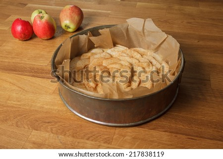 Unbaked apple pie in a metal spring form with apples lying next to it - stock photo