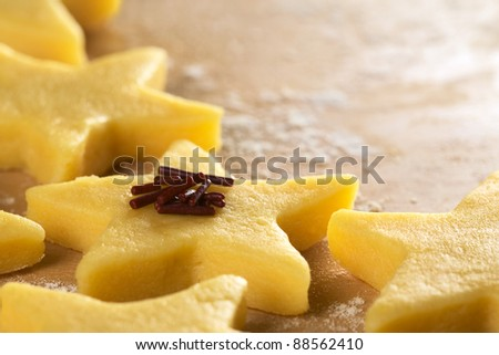 Unbaked star-shaped cookies with chocolate sprinkles on floured wooden surface (Selective Focus, Focus on the front of the chocolate sprinkles) - stock photo