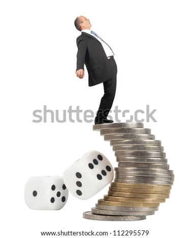 Unbalanced business man on a top of coins pile -concept of business risk