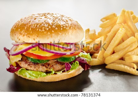 Unbearable desire. A closeup of a tempting tasty burger with red onion and vegs along with yummy french fries. - stock photo