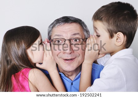 Unbelievable. Grandchildren with his grandfather and whisper something to him. Grandpa very surprised. - stock photo