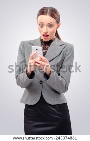 Unbelievable! Shocking news. Surprised young caucasian business woman holding mobile phone, looking at it and keeping mouth open while standing against grey background - stock photo