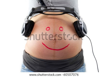 Unborn baby listening music in mother's belly - stock photo