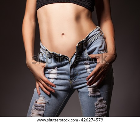 Unbuttoned jeans on beauty woman