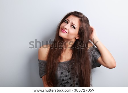 Uncertain confusion fashion makeup woman scratching the head and thinking about sales on blue background