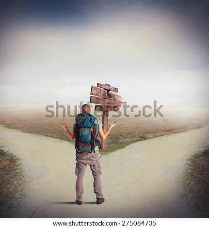 Uncertain explorer is lost at a crossroads - stock photo