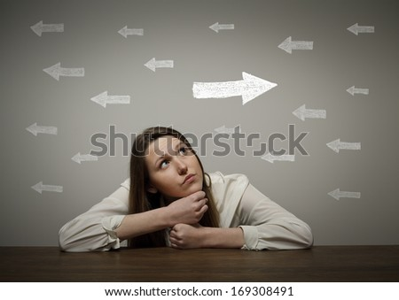 Uncertain girl is looking at arrows. Girl in white full of doubts and hesitation. - stock photo