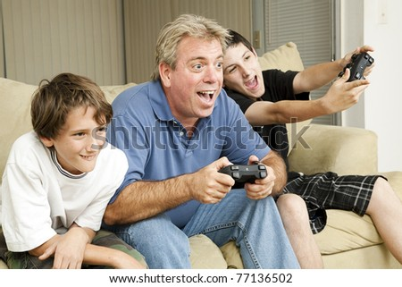 Uncle and his two nephews playing video games together.  Could also be father and sons. - stock photo