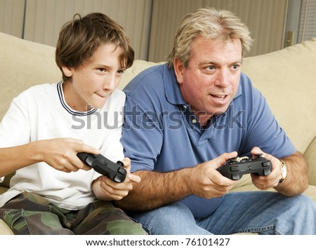Uncle and nephew (or father and son) playing video games together. - stock photo