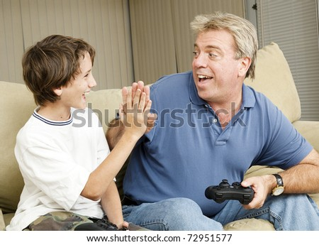 Uncle giving his nephew a high five as they play video games.  Could also be father and son. - stock photo