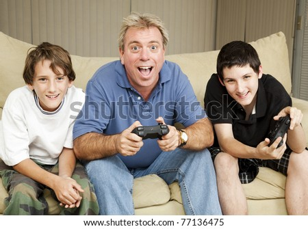 Uncle or father playing video games with two boys. - stock photo