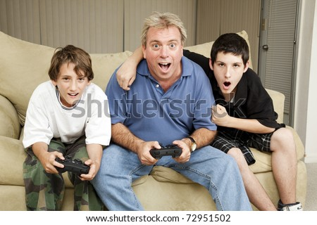 Uncle playing video games with his nephews.  Could also be dad and sons. - stock photo