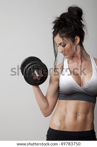 Uncluttered front view studio photo of fitness woman lifting dumbbell - stock photo