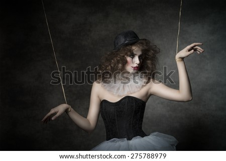 uncombed sensual woman with gothic puppet costume, uncombed hair and clown make-up. She wearing vintage tutu and bowler  - stock photo