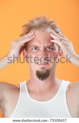 Uncomfortable young Caucasian man holds his head - stock photo