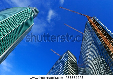 Uncompleted high-rise buildings with cranes against blue sky. - stock photo