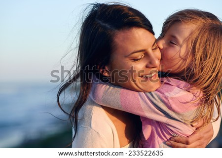 Unconditional love between mother and daughter hugging and embrace with a kiss and cuddle outdoors having fun - stock photo