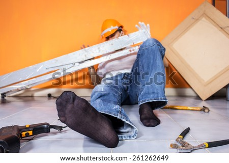 unconscious asian workman lying on the floor , focus at right foot / orange wall background - stock photo