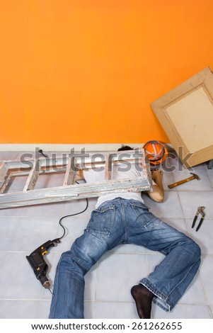 unconscious asian workman lying on the floor , orange wall background / copyspace on top - stock photo