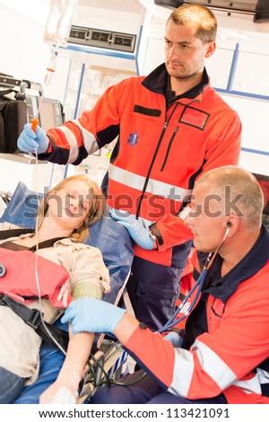 Unconscious patient woman emergency ambulance paramedics measuring blood pressure - stock photo