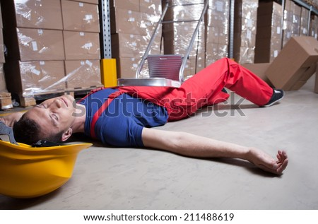 Unconscious warehouse worker after falling from a ladder  - stock photo
