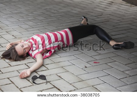 unconscious woman lying on asphalt road - stock photo
