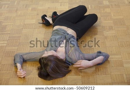 unconscious woman lying on the hardwood  flooring - stock photo