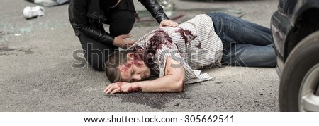 Unconscious young man is lying on street