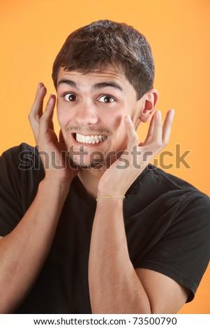 Uncontrollable joy for Latino teen on an orange background - stock photo
