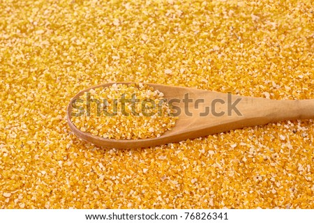 Uncoocked hominy grits  in wooden spoon - stock photo