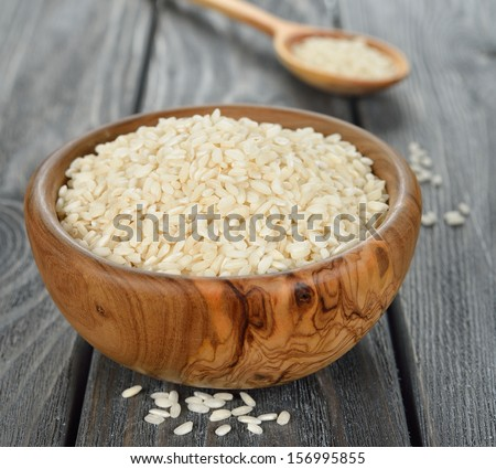 Uncooked Arborio rice in a wooden bowl on a gray table - stock photo