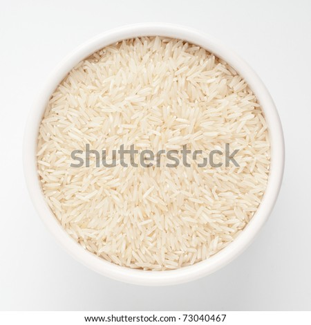 Uncooked basmati rice in a ceramic bowl on white background - stock photo