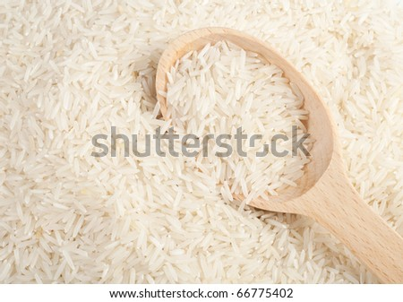 Uncooked basmati rice in a wooden spoon - stock photo