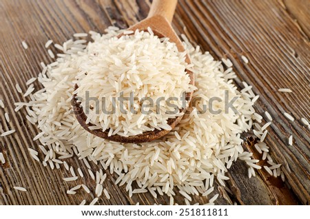 Uncooked basmati rice in  wooden  spoon . Selective focus - stock photo
