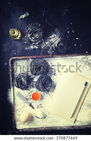 Uncooked black pasta and ingredients for homemade spaghetti Italian food.Notepad to write the prescription.Toned image.Vintage style.Copy space.selective focus - stock photo