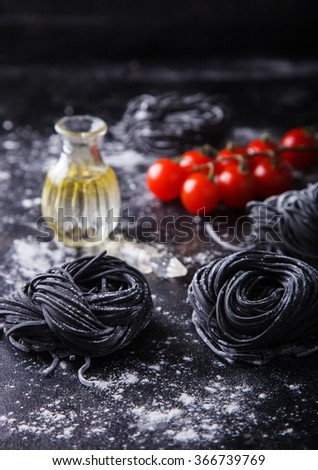 Uncooked black pasta and ingredients for homemade spaghetti Italian food on a dark background.selective focus. - stock photo