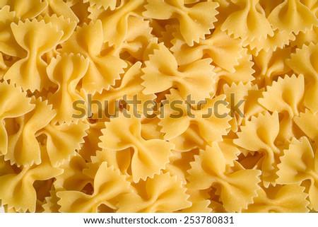 Uncooked bow tie pasta background (italian farfalle) - stock photo
