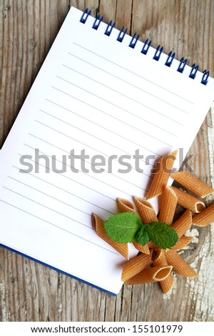 Uncooked brown pasta selection on a wooden rustic background with an empty note book, recipe time concept, old retro vintage style